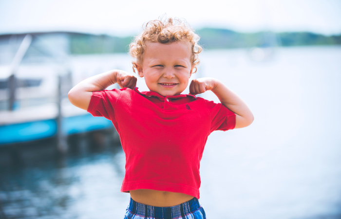 Curly haired young boy in a red polo flexes his arms in a strong-man pose and smiles by a lake