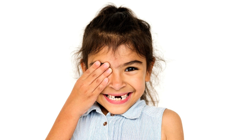 young girl covering one eye missing several baby teeth