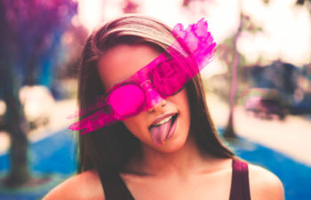 girl wearing rose colored glasses sticking out her tongue