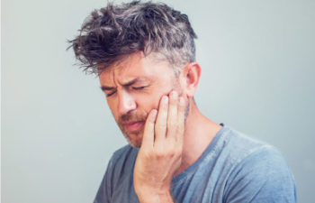 man holding his jaw with TMJ disorder pain