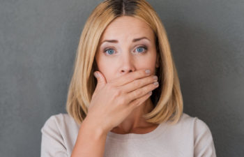 woman covering her mouth to hide discolored teeth