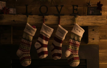 four Christmas stocking along the mantle held up with love holders