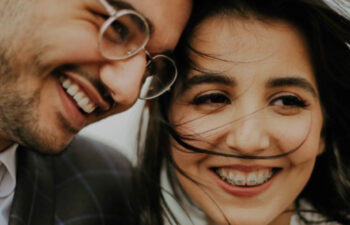 young couple wearing different kinds of braces smile at each other
