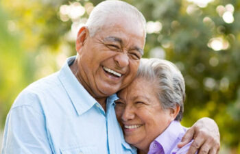 senior couple hug and smile after learning about the benefits of dental implants
