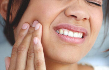 woman holds her cheek in pain from a tooth infection needing a root canal